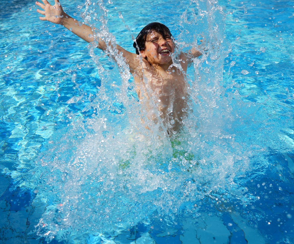 Happy little boys enjoying relaxing and splashing in water