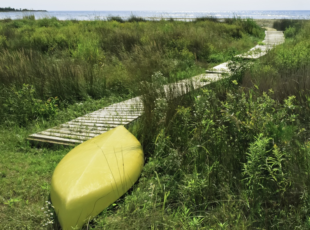 Yellow kayak, upside down, at end of boardwalk to beach-1